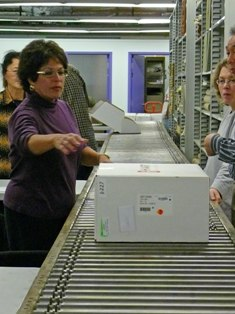 Reaching for a Judge's Booth Controller box off the conveyor at the Mock Election