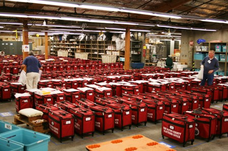 Unpacking red suitcases filled with precinct supplies at elections headquarters.