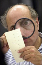 Inspecting hanging chads with a magnifier during the 2000 Presidential Election