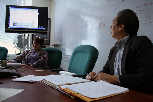 Listening to feedback from poll workers via teleconference while calls were monitored onscreen