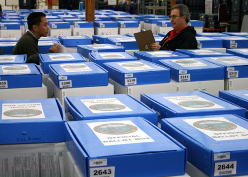 Checking numbers and barcodes on red suitcases, white JBC boxes and blue ballot boxes
