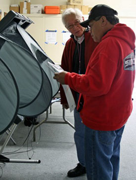 A poll worker helping a voter use the eSlate at a polling place on Election Day