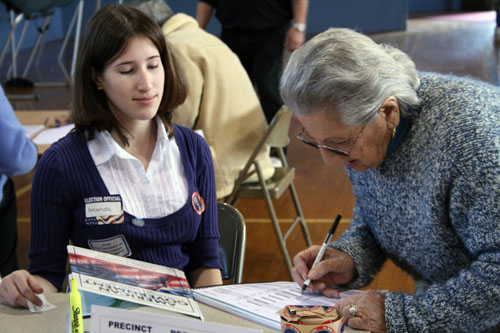 Student poll worker helping a voter sign the roster at Spruce ElementarySchool
