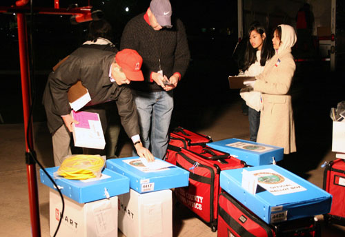 Red supply suitcases, blue paper ballot boxes and JBCs being collected at a receiving station in Menlo Park